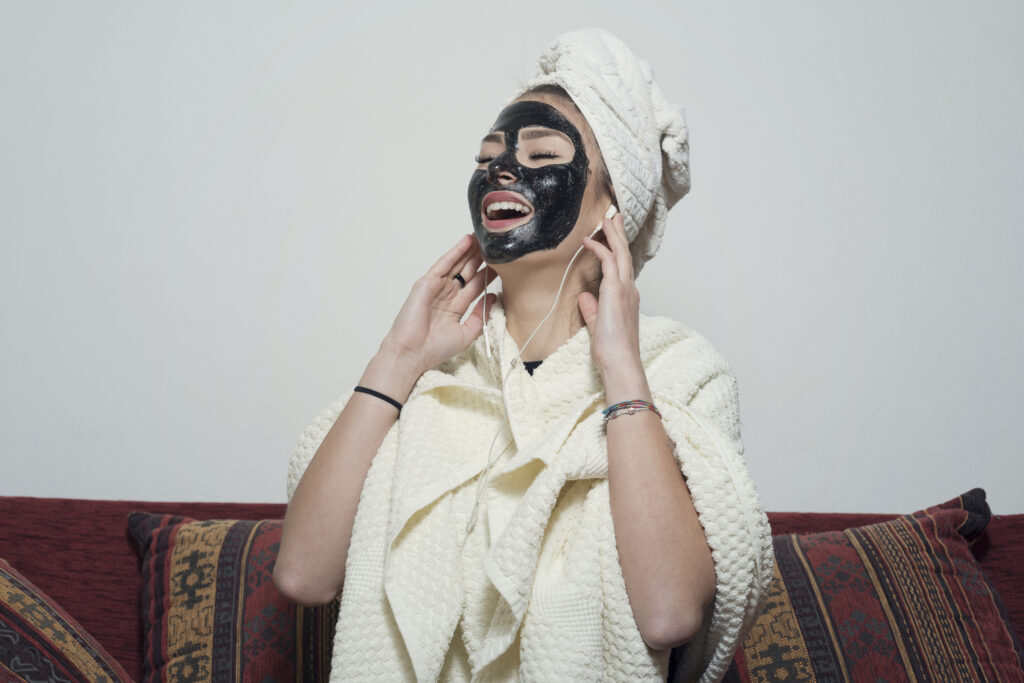 Woman sitting on sofa wearing facial mask, Listening music with headphone