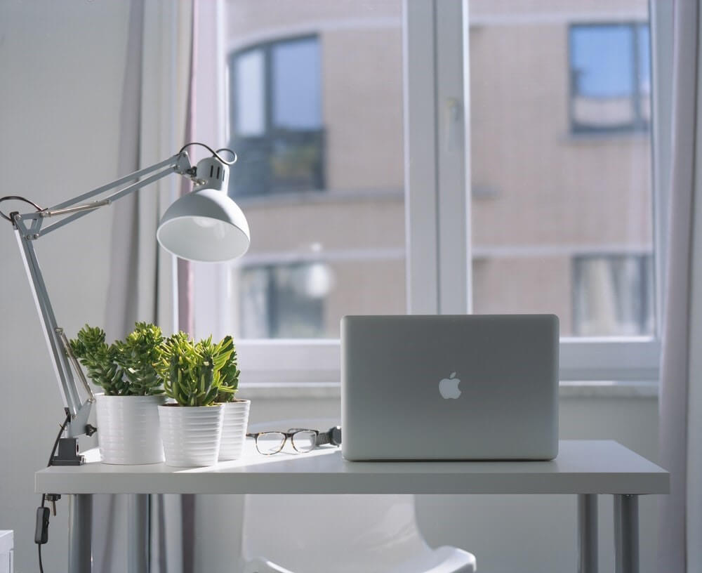 silver MacBook on top of white wooden desk