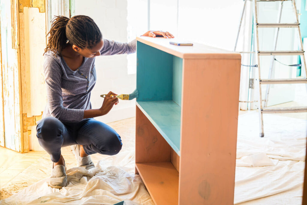 A women repainting an old bookcase.