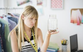 woman looking at a jar with money