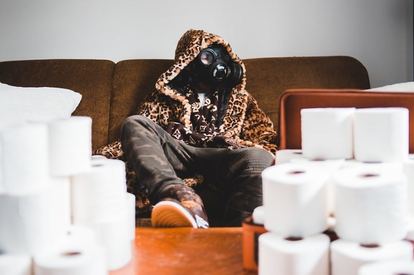 A man sat in a gas mask on his sofa, surrounded by toilet rolls.