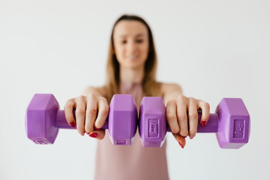 Defocused content young female doing bicep exercise with dumbbells during functional training in light studio