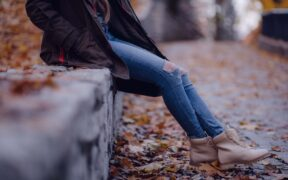 A Ladie sitting among fallen leaves wearing winter boots